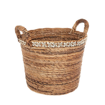 Banana leaf basket in hand decorated with shells